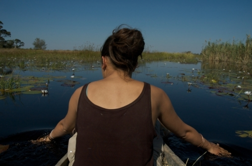on the narrow makoro sailing through water lilies