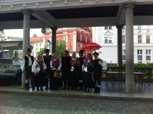 traditional Slovenian costume, in front of the pink church