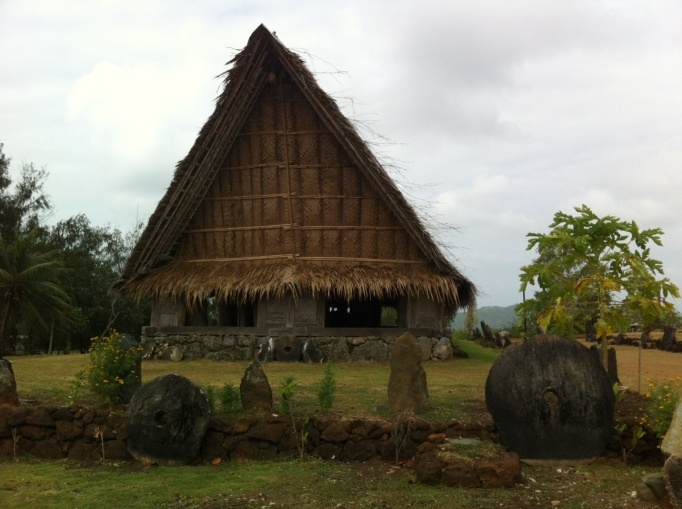 a traditional Yapese house and some stone money around it