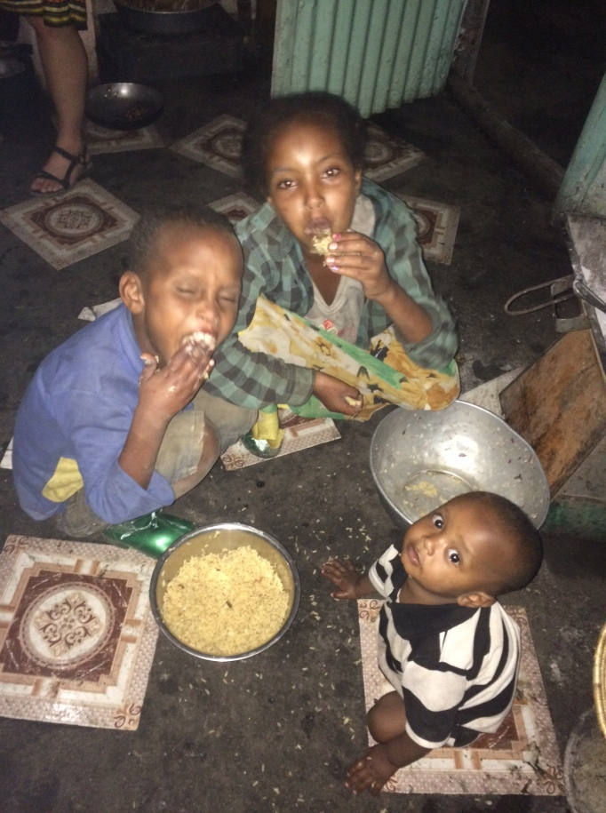 the street kids in Hirna, Ethiopia, offer to share their dinner